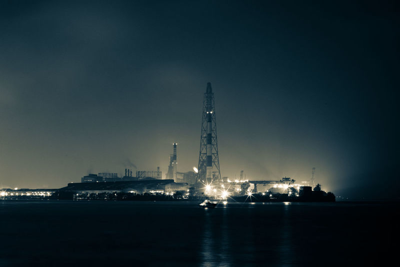 Illuminated factory by sea against sky at night