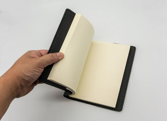 Close-up of hand holding book against white background