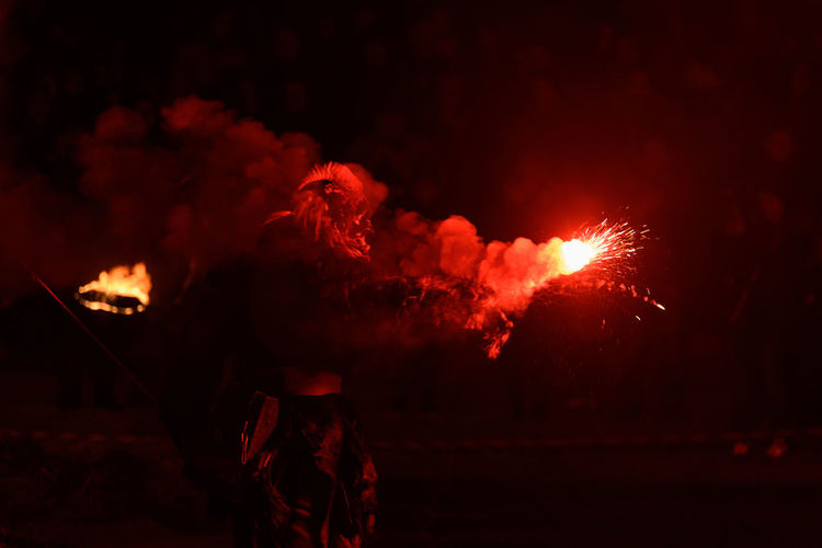 Person wearing costume while holding sparks at night