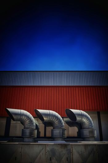 Low angle view of industry against clear blue sky