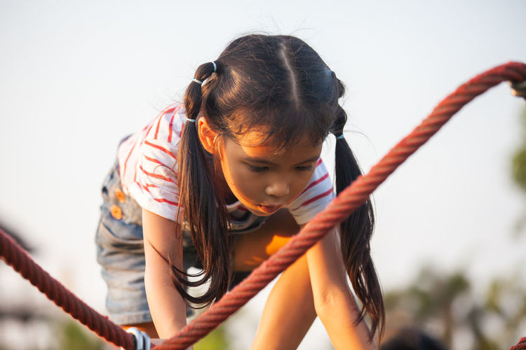Girl climbing on jungle gym against clear sky