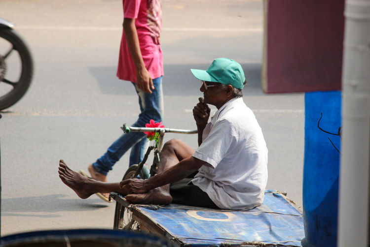 Side view of people sitting on street
