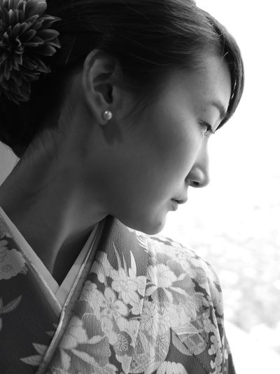 Close-up of young woman in kimono looking away