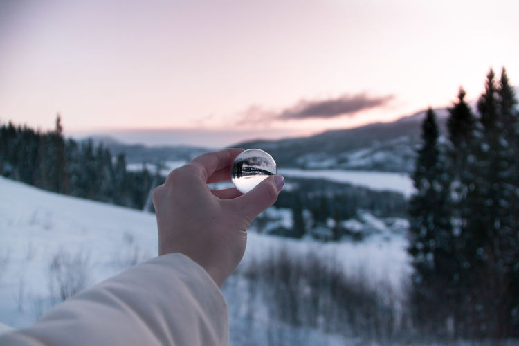 Cropped hand of person holding crystal ball against landscape during winter