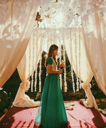 Side view of bride holding bouquet while standing at wedding ceremony