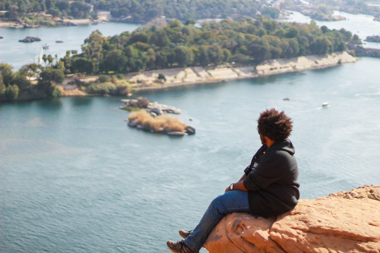 Man Sitting On Cliff By Nile River
