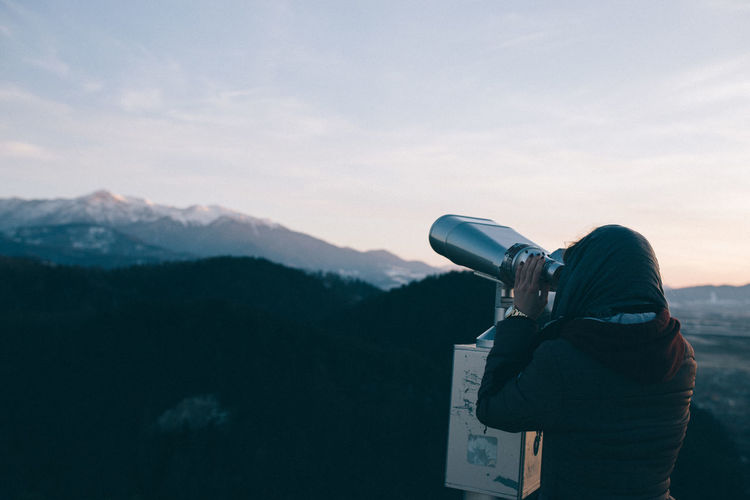 Woman looking at mountains through coin-operated binoculars against sky
