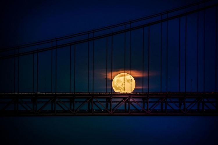 Silhouette suspension bridge against moon at night