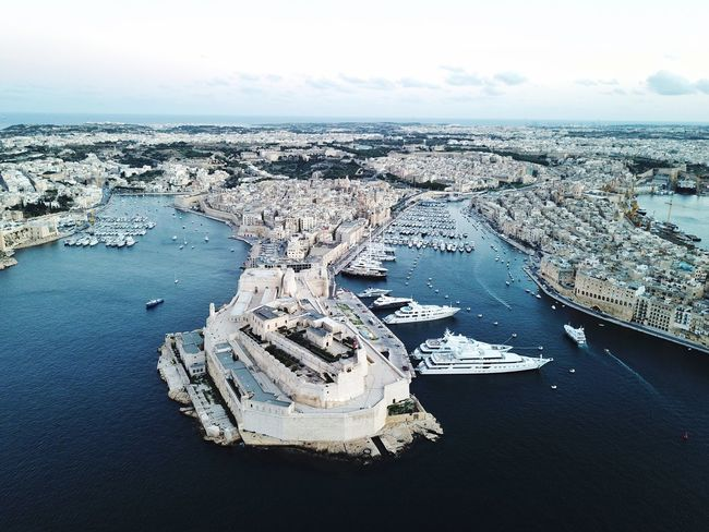An aerial view of Vittorosa city 'Birgu' and the Grand Harbour in Malta. Fortification Fortress Senglea The Three Cities Cospicua Drone Photography Drone  Aerial Aerial View Peninsula Urban Scene Urban Luxury Boats Malta Marina Boats Yacht Luxury Birgu Vittoriosa Valletta Grand Harbour Harbour Water Sky Sea Nature Land Tranquility High Angle View