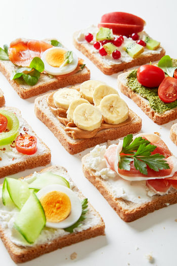 Sandwiches variation with vegetables, fruits, meat, eggs and sweets viewed from above. Variety of bruchetta breads arranged for a tasty and healthy breakfast. Food Freshness Still Life Healthy Eating Bread Ready-to-eat No People Apetizer Breakfast Bruchetta  Cheese Fresh Delicious Meal Lunch Lettuce Ham Plate Sandwich Selection Variation Variety Snack