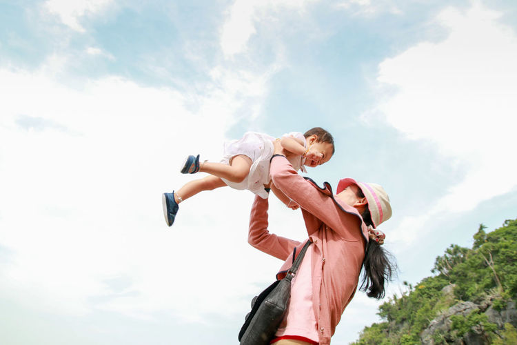 Happy family concept, Young mother jolly with her baby Bonding Carrying On Shoulders Childhood Cloud - Sky Daughter Day Family With One Child Father Girls Happiness Leisure Activity Love Low Angle View Mother Nature Outdoors Piggyback Real People Sky Smiling Togetherness Tree Women Young Adult Young Women