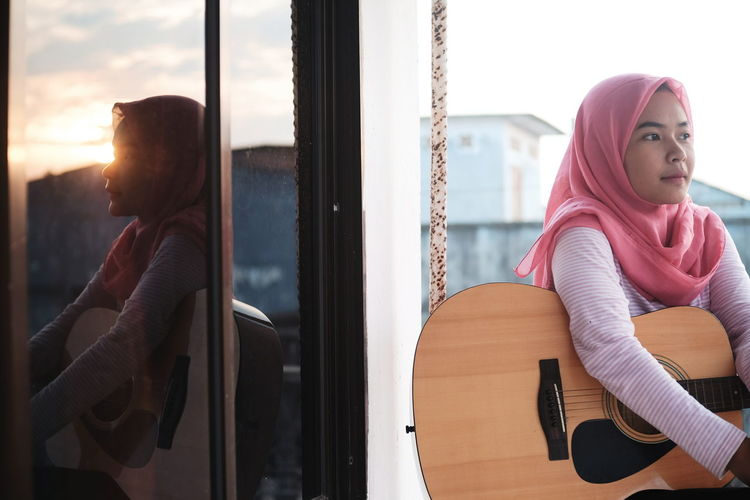Sunset Portrait Warm Clothing Young Women Guitar Window Looking Through Window Music Knit Hat Arts Culture And Entertainment Scarf Sitting Guitarist Classical Guitar Acoustic Guitar Musical Instrument String Acoustic Music