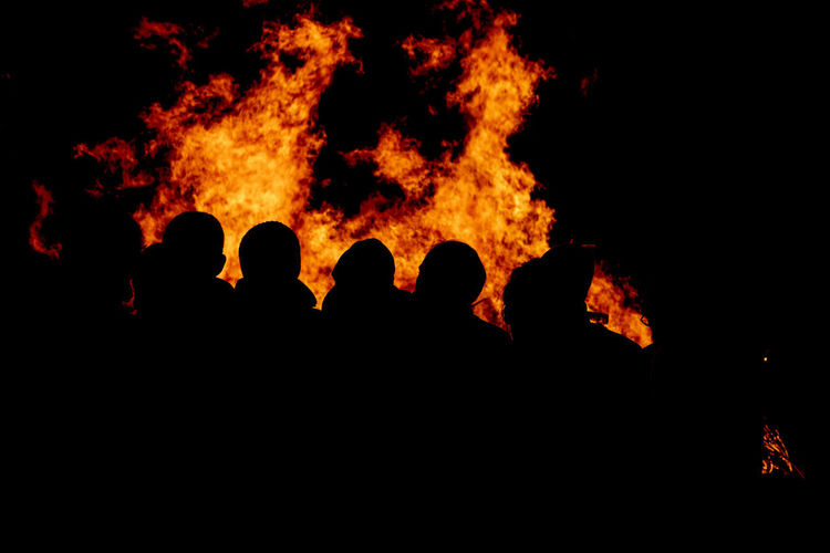 Silhouette people against fire at night