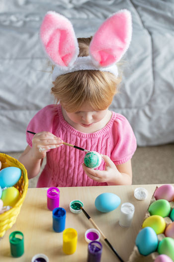 Little girl in easter bunny ears painting colored eggs. easter at home and craft concept.