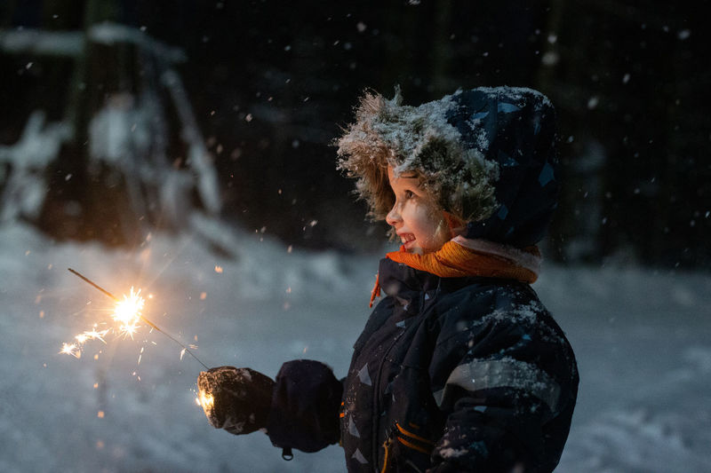 Toddler girl in winter clothes walking outside and holding sparkler in her hand. dark and snowy