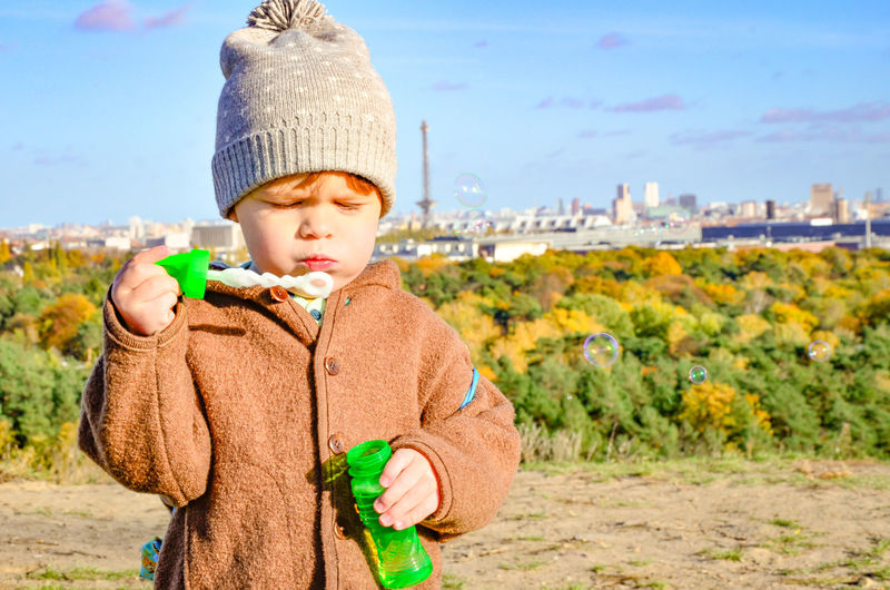 Little boy plays with soup bubbles in front of great autumn Berlin panorama. Berlin Bubbles Colourful Green Kindergarten Panorama Trees Boys Childhood Close-up Front View Horizon One Person Play Real People Sky Soup Soup Bubbles Teufelsberg Warm Clothing Second Acts