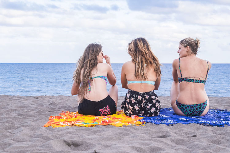 three beautiful nice young ladies viewed from rear sitting at the beach enjoying vacation and travel destination looking the ocean. relaxing and speaking in friendship together. ocean summer destination concept Rear View Adult Beach Beach Towel Bikini Clothing Cloud - Sky Friendship Horizon Over Water Land Leisure Activity Lifestyles Long Hair Nature Outdoors Real People Sea Sitting Sky Swimwear Three People Trip Vacations Water Women