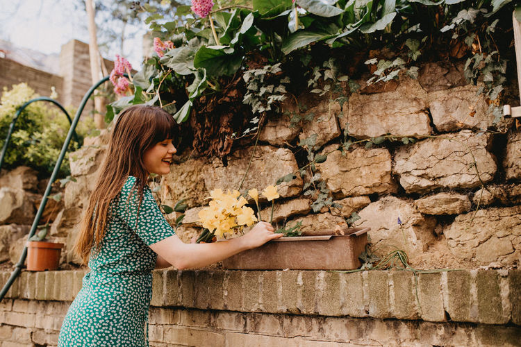 Side view of smiling woman looking flowers