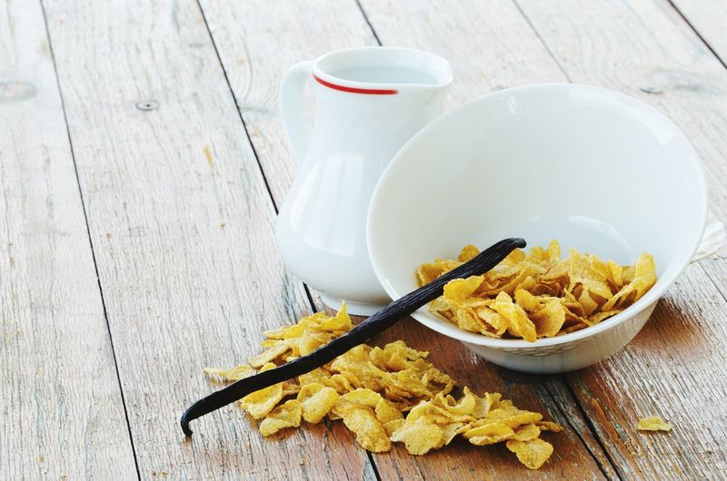 High angle view of vanilla pod on corn flakes bowl by milk on table