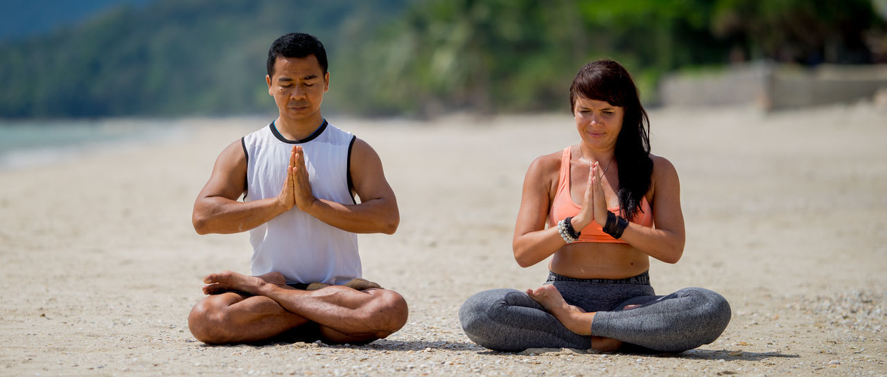 Adult Beach Beautiful Woman Beauty In Nature Cross-legged Day Focus On Foreground Healthy Lifestyle Lifestyles Lotus Position Meditating Men Nature Outdoors Real People Relaxation Sand Sitting Togetherness Two People Water Wellbeing Yoga Young Adult Young Women