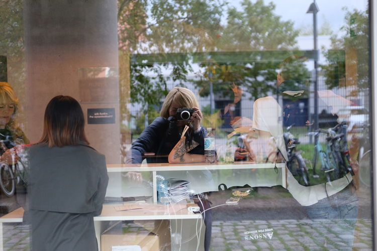 Reflection of woman photographing on window at store
