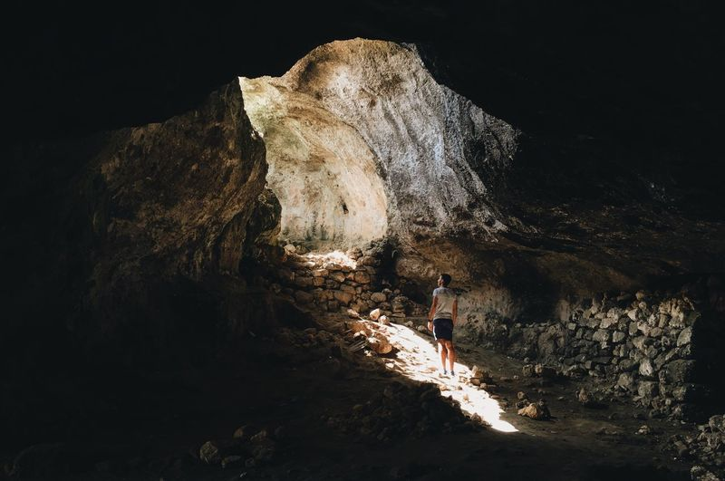 Rear view of woman standing on rock formation in cave