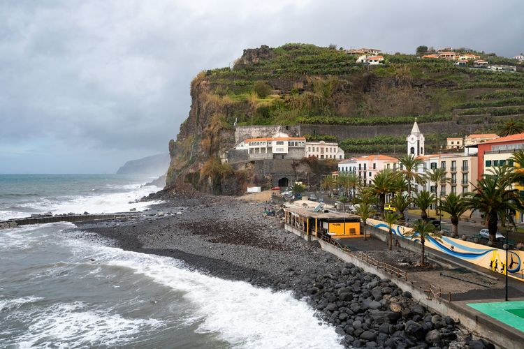 View of Ponta do Sol village in Madeira Architecture City Cityscape Madeira Nature Panorama Panoramic Portugal Portuguese Travel Architecture Beach Black Rock Beach Black Sand Beach Europe Island Landscape Mountain Outdoors Rocks Sea Seascape Town Water Waves
