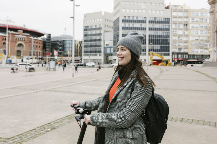 Portrait of smiling young woman standing on street in city