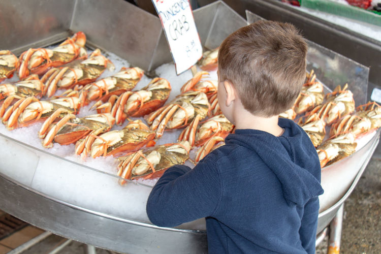 Full length of boy eating food at market stall
