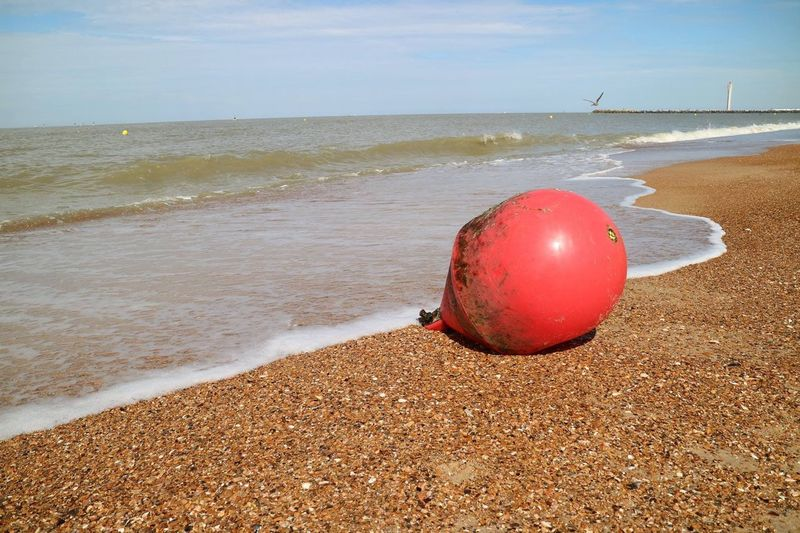 Red Ball On Sand At Beach Against Sky