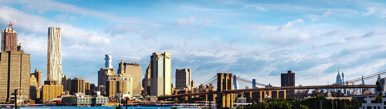 Panoramic view of bridge and buildings against sky