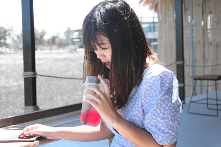 Woman drinking juice while using mobile phone in cafe
