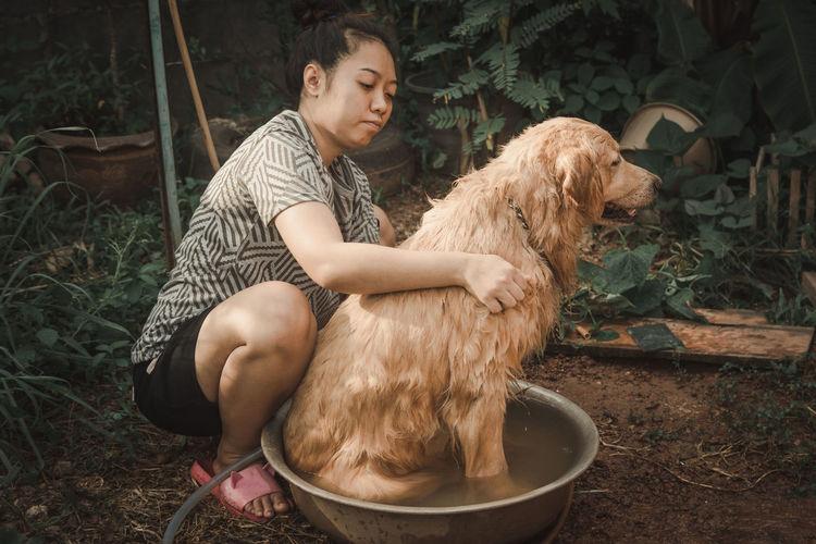 Woman bathing dog against plants