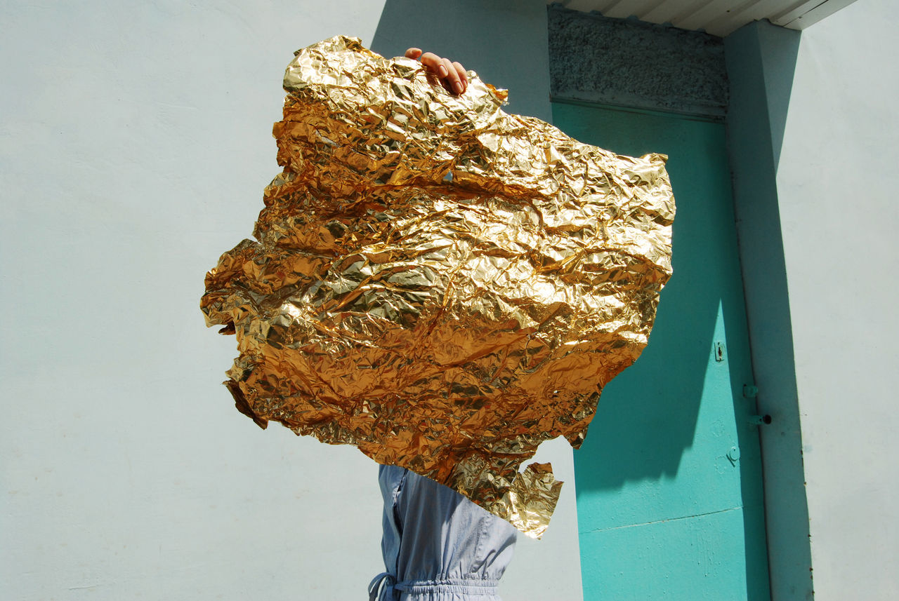 Golden foil held by woman outside house