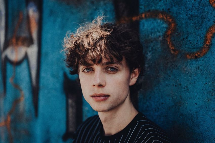 Portrait Headshot Looking At Camera One Person Young Adult Front View Child Real People Lifestyles Serious Young Women Teenager Curly Hair Blue Day Boys Young Men Wall - Building Feature Close-up Adolescence
