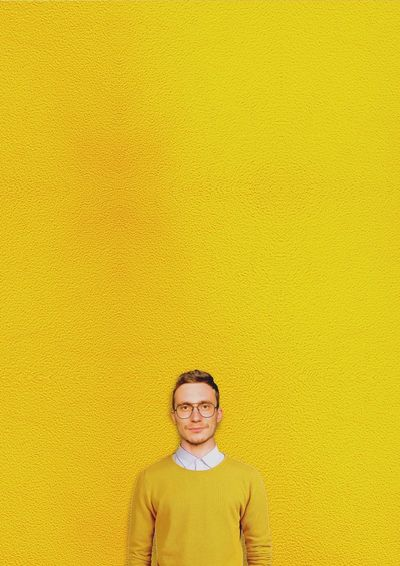 Lemon Yellow Front View Looking At Camera Portrait One Person Smiling Copy Space Looking At Camera Copy Space Casual Clothing Glasses Standing Wall - Building Feature Happiness Young Adult Indoors  Yellow Background Studio Shot Colored Background Eyeglasses  Hairstyle