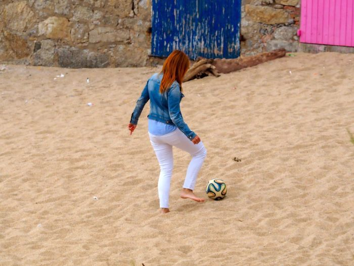 Full length of woman playing soccer at beach