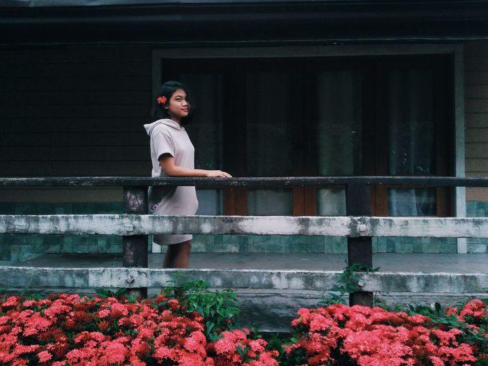 Full length portrait of woman against pink flowering plants