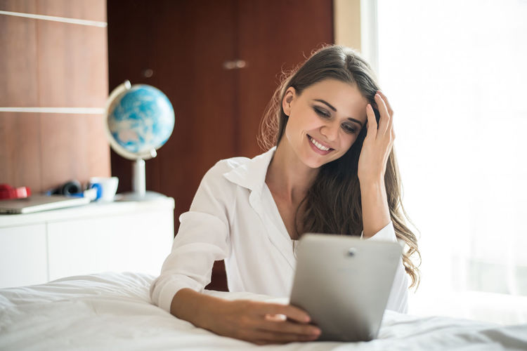 Young Adult One Person Technology Bed Young Women Wireless Technology Indoors  Communication Lifestyles Domestic Room Real People Sitting Beauty Smiling Furniture Connection Bedroom Front View Women Beautiful Woman Hair Hairstyle Using Laptop