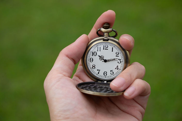 Close-up of human hand holding pocket watch