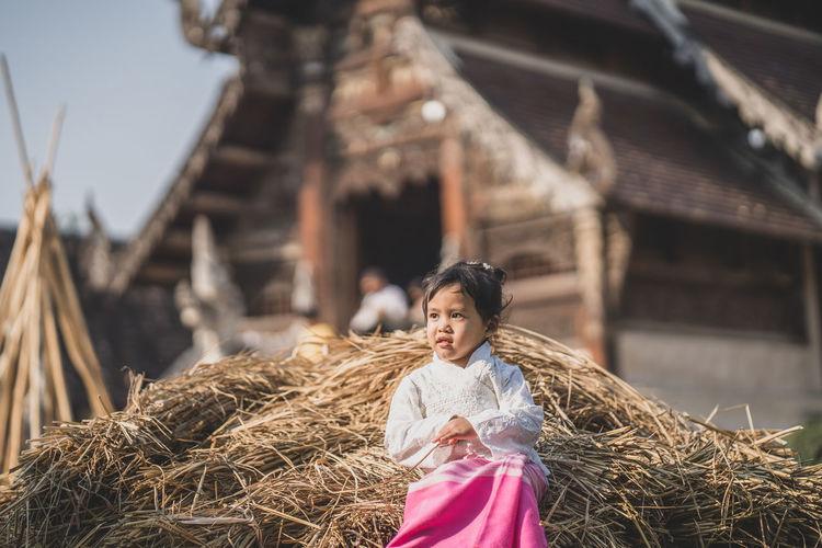 Girl looking away sitting on haystack against barn