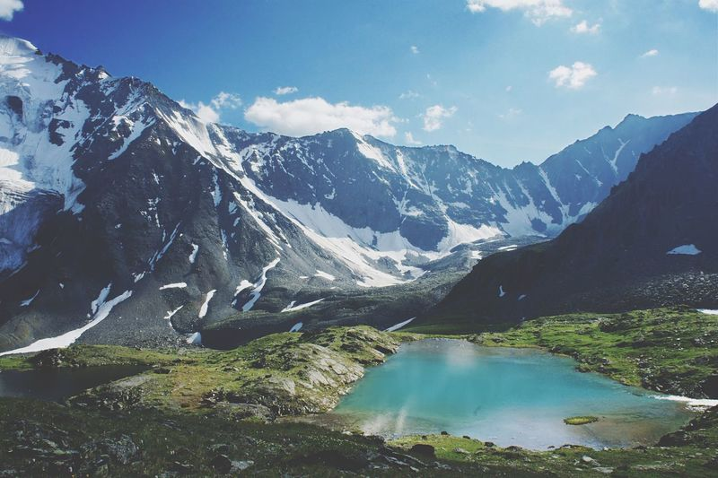 Scenic view of lake amidst mountains against sky during sunny day