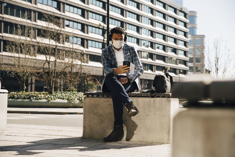 Man sitting against building in city