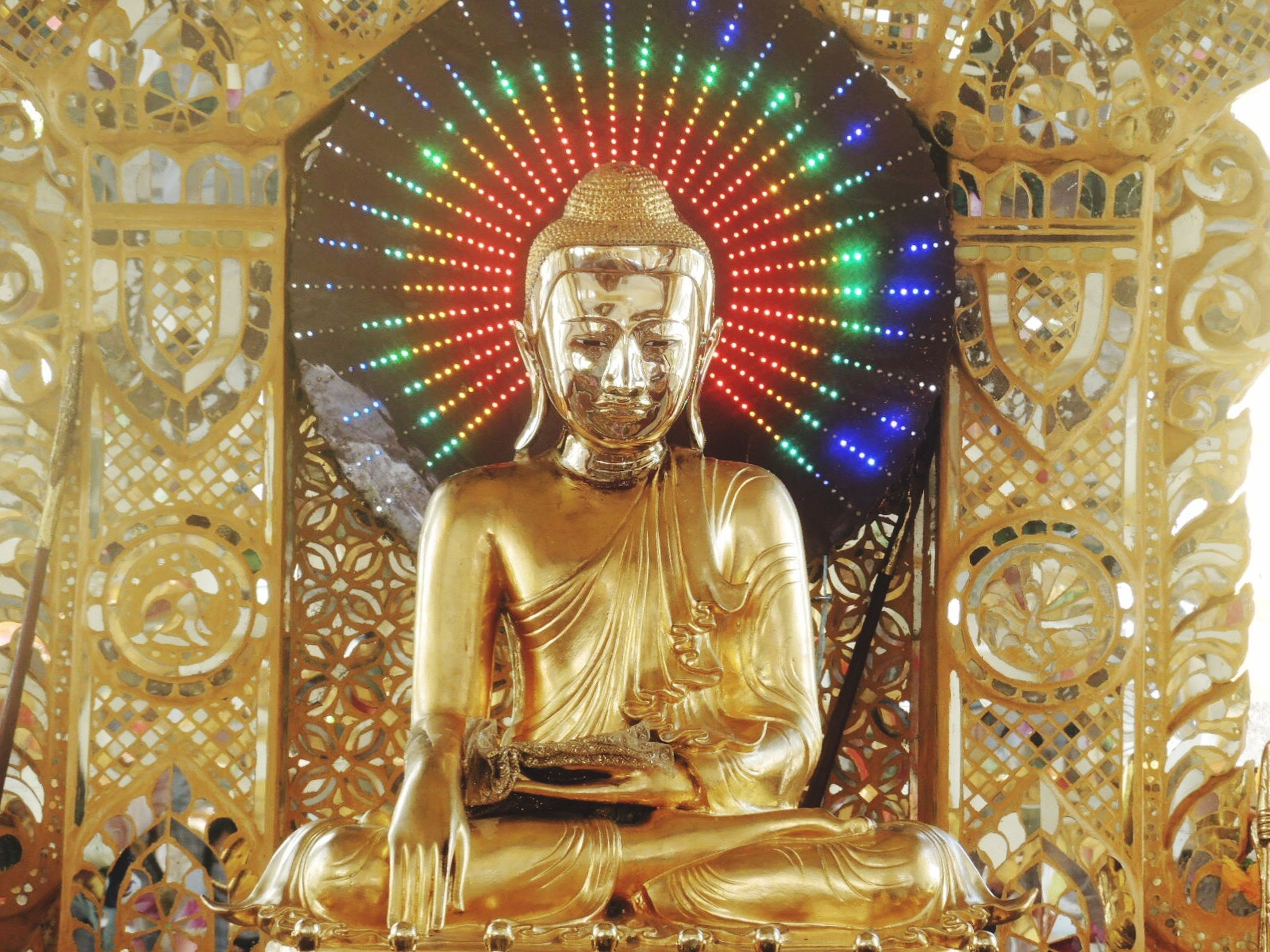 human representation, statue, spirituality, sculpture, religion, art and craft, indoors, low angle view, buddha, art, place of worship, gold colored, creativity, idol, gold, golden color, lens flare, history