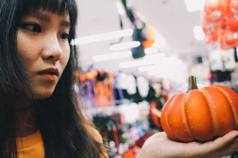 Portrait of woman holding pumpkin at home
