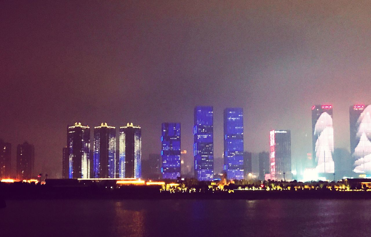 illuminated, architecture, night, built structure, building exterior, city, waterfront, skyscraper, cityscape, travel destinations, water, modern, sea, no people, urban skyline, outdoors, sky, nature
