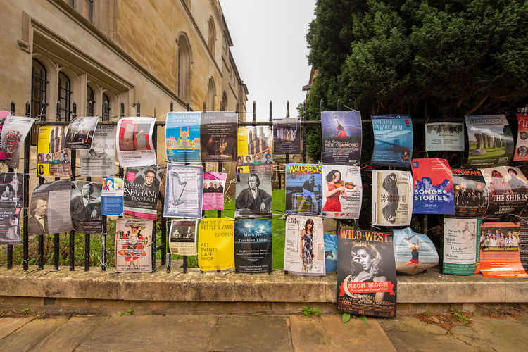 An iron railing fence covered in colourful flyers and posters promoting concerts and performances. A common sight in Cambridge, UK. Advertising City Center Architecture Cambridge Choice City Communication Concerts Day Flyers In A Row Large Group Of Objects Multi Colored No People Outdoors Performances Plant Posters Street Text Tree Variation Western Script