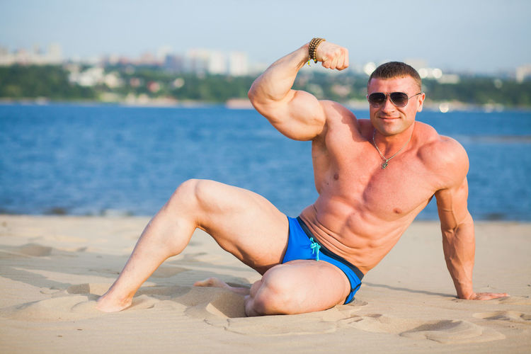 Portrait of shirtless bodybuilder while standing on beach against bay of water