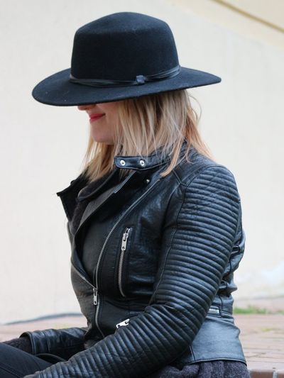 Woman wearing leather jacket and hat