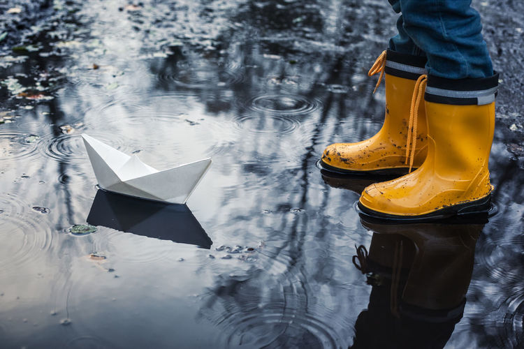 Low section of boy standing by paper boat in puddle